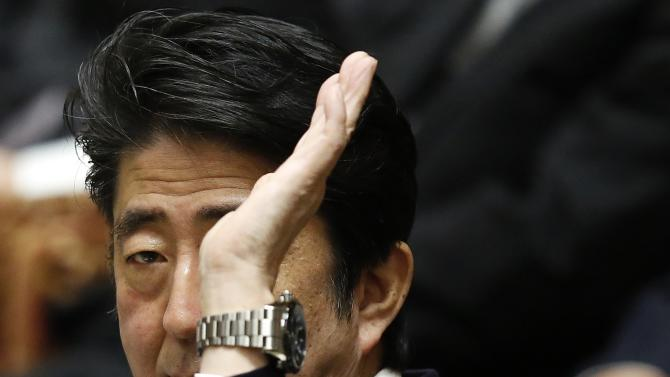 Japan's PM Abe rises his hand to answer a question during a lower house committee session at the parliament in Tokyo