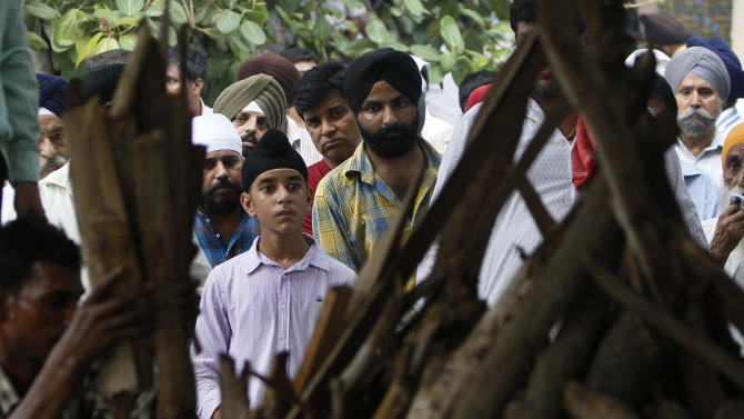 A boy looks at the funeral pyre of his blast victim and grandfather Inder Singh during his cremation in New Delhi, India, Thursday, Sept. 8, 2011. Indian authorities were questioning an Internet cafe owner and two other people Thursday as they scrambled for leads into a powerful briefcase bomb that tore through the crowds outside a New Delhi courthouse. (AP Photo/Gurinder Osan)