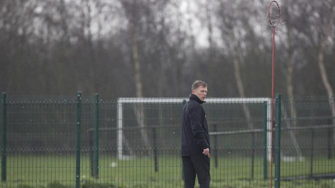 Manchester United's manager David Moyes walks between pitches as his team train at Carrington training ground in Manchester, Tuesday, March 18, 2014. Manchester United will play Olympiakos in a Champions League last 16 second leg soccer match on Wednesday