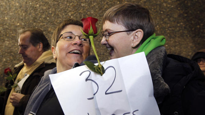 Melody Platt, left, and her partner Beratta Gomillion wait among the first couples in line to be issued a marriage license to a same-sex couple, Wednesday, Dec. 5, 2012, in Seattle. King County Executive Dow Constantine was to began issuing the licenses just after midnight, Thursday, Dec. 6, immediately upon certification of the November election that passed Referendum 74 allowing same-sex couples to wed. The couple are planning on getting married on their 32nd anniversary, Monday Dec. 12. (AP Photo/Elaine Thompson)