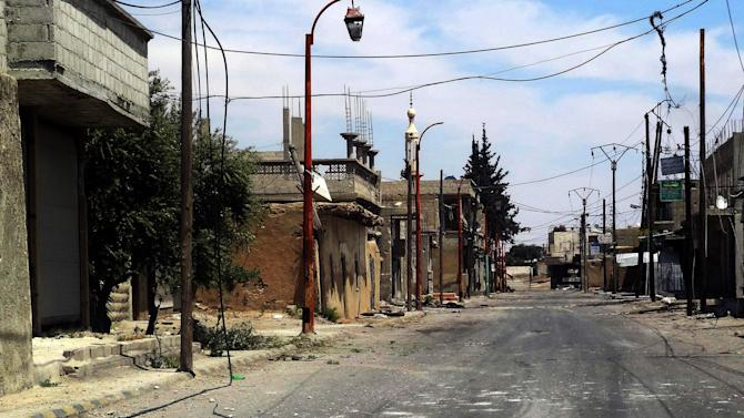 This Wednesday, April 24, 2013 photo released by the Syrian official news agency SANA, shows a damaged street in Otaybah town, east of Damascus, Syria. After five weeks of battle, Syrian government troops captured a strategic town near Damascus, cutting an arms route for rebels trying to topple President Bashar Assad's regime, state media and activists said Thursday. (AP Photo/SANA)