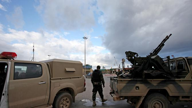 A member of the Libyan security forces stands guard near his armored vehicle on the early morning of the second anniversary of the revolution that ousted Moammar Gadhafi, in Benghazi, Libya, Sunday, Feb. 17, 2013.  (AP Photo/Mohammad Hannon)
