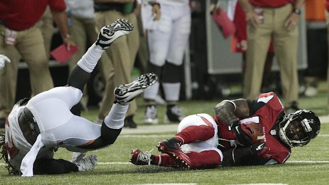 Atlanta Falcons wide receiver Devin Hester (17) recovers the ball after Tampa Bay Buccaneers cornerback Alterraun Verner (21) fumbled during the first half of an NFL football game, Thursday, Sept. 18, 2014, in Atlanta
