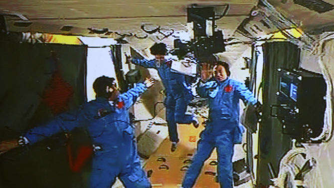 In this image made off the monitor screen at the Beijing Aerospace Flight Control Center and released by China's Xinhua News Agency, Chinese astronaut Liu Wang, left, tries to help his female colleague Liu Yang move forward as their commander Jing Haipeng waves in the orbiting Tiangong-1 lab module Monday afternoon, June 18, 2012. They moved from Shenzhou-9 spacecraft to this module three hours after docking Monday. (AP Photo/Beijing Aerospace Control Center via Xinhua) NO SALES