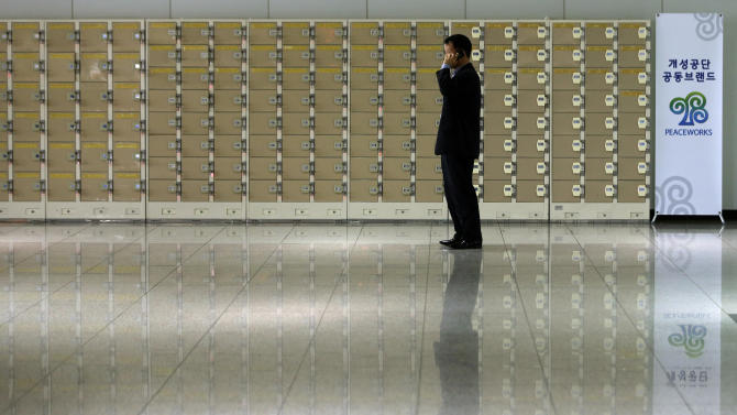 A South Korean man uses his mobile phone in front of empty lockers which are used for worker's belongings before leaving for the North Korean city of Kaesong, at the customs, immigration and quarantine office near the border village of Panmunjom, that has separated the two Koreas since the Korean War, in Paju, north of Seoul, South Korea, Monday, April 8, 2013. North Korea raised tensions Wednesday when it barred South Koreans and supply trucks from entering the Kaesong industrial complex, where South Korean companies have employed thousands of North Korean workers for the past decade.(AP Photo/Lee Jin-man)