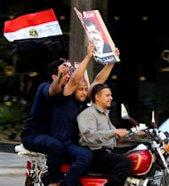 Egyptians waving their national flag and a poster of their new president-elect, Muslim Brotherhood candidate, Mohamed Morsi, arrive on a motorbike in Cairo&#39;s Tahrir Square to celebrate Morsi&#39;s victory in Egypt&#39;s presidential elections