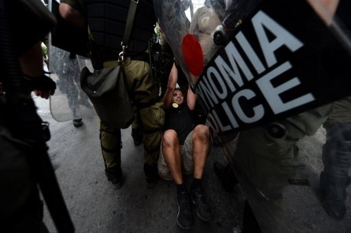 "<p>Riot police detain a protestor in Athens during a demonstration against the vist of Angela Merkel. The German Chancellor told Greece that the ""tough path"" of painful spending cuts will pay off, as tens of thousands of protesters massed in the capital.</p>"