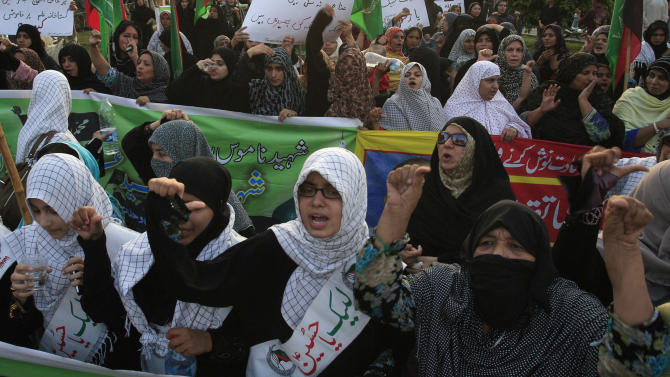 """Pakistani Shiite Muslim women chant anti U.S. slogans during a demonstration that is part of widespread anger across the Muslim world about a film ridiculing Islam's Prophet Muhammad, Sunday, Sept. 23, 2012 in Lahore, Pakistan. The woman, center, wear a banner that reads, """"at your service Hussein."""" (AP Photo/K.M. Chaudary)"""