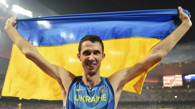 Third placed Bondarenko of Ukraine celebrates with a national flag after winning bronze in the men's high jump final during the 15th IAAF World Championships at the National Stadium in Beijing