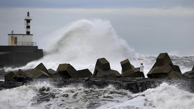 A man stands while huge waves crash on the San Esteban de Pravia seafront