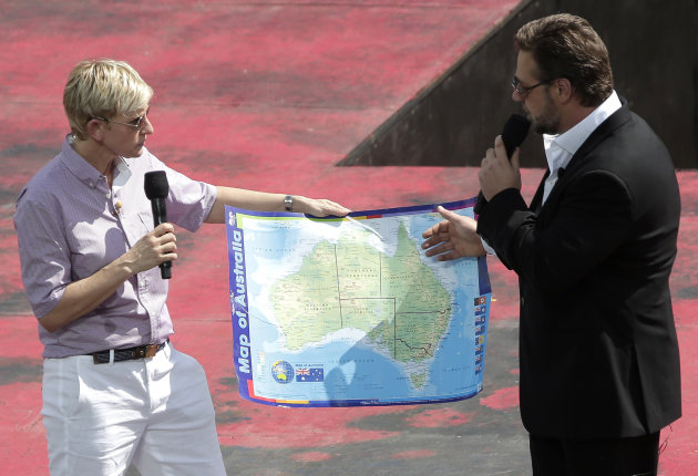 U.S. talk show host Ellen DeGeneres, left, has actor Russell Crowe show her a map of Australia during a recording of her show in Sydney, Australia, Saturday, March 23, 2013.(AP Photo/Rick Rycroft)