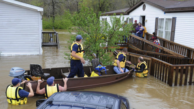 Firefighters rescue a family from their home, surrounded by floodwaters, in a mobile home park in Pelham, Ala., on Monday, April 6, 2014. Overnight storms dumped torrential rains in central Alabama, causing flooding across a wide area. (AP Photo/Jay Reeves)