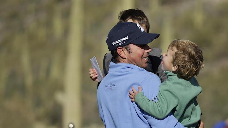Matt Kuchar picks up his children Cameron and Carson after defeating Hunter Mahan 2 and 1 in the final round of play during the Match Play Championship golf tournament, Sunday, Feb. 24, 2013, in Marana, Ariz. (AP Photo/Julie Jacobson)