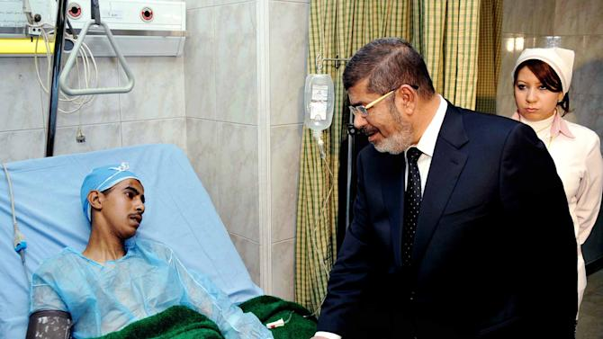 In this image released by the Egyptian Presidency, Egyptian President Mohammed Morsi, right, visits a victim receiving treatment following a train crash in Badrasheen, 40 Kilometers (25 miles) south Cairo at a military hospital in Cairo, Egypt, Tuesday, Jan. 15, 2013. At least 19 people died and more than 100 were injured when two railroad passenger cars derailed just south of Cairo, health officials say. The accident comes less than two weeks after a new transportation minister was appointed to overhaul the rail system, and just two months after a deadly collision between a train and school bus. (AP Photo/Egyptian Presidency)