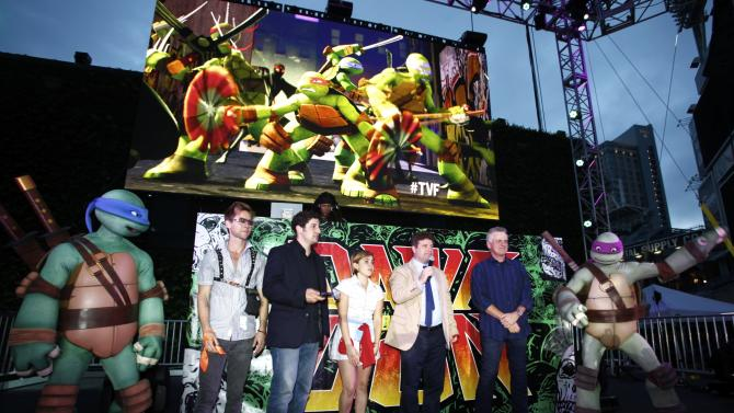 COMMERCIAL IMAGE - Cast members of 'Teenage Mutant Ninja Turtles' Greg Cipes, Jason Biggs, Mae Whitman, Sean Astin and Rob Paulsen pose for a photo with the teenage mutant ninja turtles at the Dawn Of The Con at Petco park during Comic-Con on Wednesday, July 12, 2012, in San Diego, Calif. (Photo by Joe Kohen/Invision for Nickelodeon/AP Images)