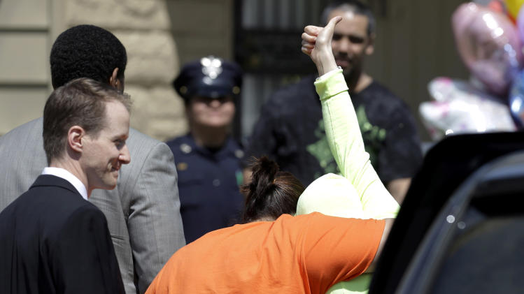 AP10ThingsToSee - Gina DeJesus gives a thumbs-up as she is escorted toward her home Wednesday, May 8, 2013, in Cleveland. Police say DeJesus is one of three women and a child who were held captive for about a decade at a run-down house in Cleveland. The home-owner is under arrest and has been charged with kidnapping and rape. (AP Photo/Tony Dejak, File)