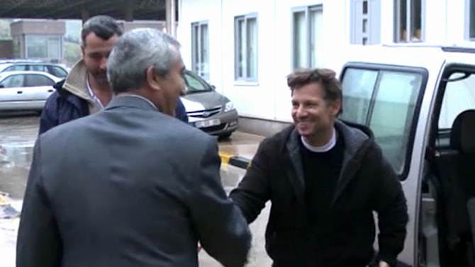 """In this image made from video, NBC chief foreign correspondent Richard Engel, right, shakes hands with an unidentified person after crossing back into Turkey, after they were freed unharmed following a firefight at a checkpoint after five days of captivity inside Syria, in Cilvegozu, Turkey, Tuesday, Dec. 18, 2012. Engel told the Turkish news agency Anadolu that he and his colleagues are """"very happy to be out"""" and they are """"very tired."""" (AP Photo/Anadolu via AP TV) TURKEY OUT, TV OUT"""
