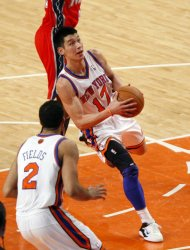 New York Knicks point guard Jeremy Lin (C) drives to the basket during their NBA basketball game against the New Jersey Nets at Madison Square Garden in New York February 20, 2012. REUTERS/Eduardo Munoz (UNITED STATES - Tags: SPORT BASKETBALL)