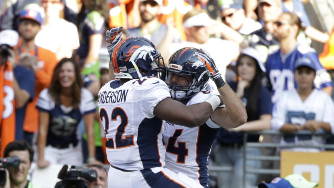 Denver Broncos tight end Jacob Tamme, right, celebrates with C.J. Anderson (22) after Tamme scored a touchdown in the second half of an NFL football game against the Seattle Seahawks, Sunday, Sept. 21, 2014, in Seattle. (AP Photo/Elaine Thompson)