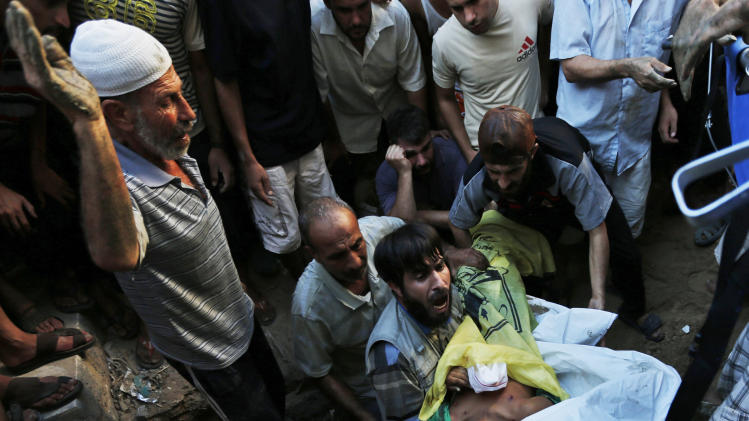A mourner lowers the body of one of four boys killed in an Israeli strike, during their funeral in Gaza City on Wednesday, July 16, 2014. The four boys, who were cousins and ages 9 to 11, were killed while playing on a beach off a coastal road west of Gaza City, said Ashraf Al Kedra, a Palestinian doctor. Seven others - adults and children - were wounded in the strike, he said. (AP Photo/Lefteris Pitarakis)