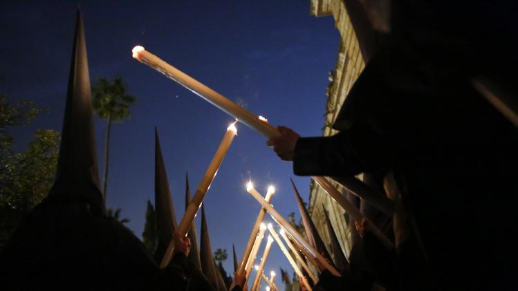 Penitents of Los Estudiantes (The Students) brotherhood hold candles as they take part in a Holy Week procession in the Andalusian capital of Seville