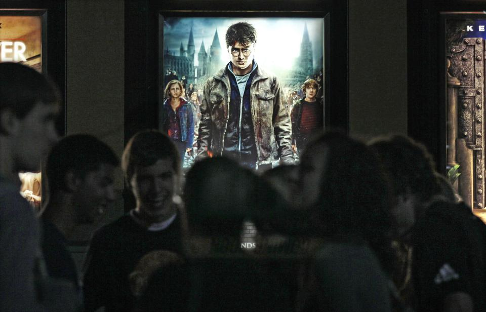 "Moviegoers wait  for the midnight showing of ""Harry Potter and the Deathly Hallows Part II"" in Merrimack, N.H., Thursday, July 14, 2011.  The film is expected to put up franchise-record numbers as it debuts just after midnight Friday.(AP Photo/Charles Krupa)"
