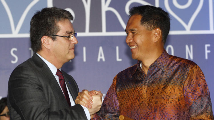Indonesian Trade Minister Gita Wiryawan, right, shakes hands with World Trade Organization (WTO) Director-General Roberto Azevedo, left, during the closing ceremony of the ninth WTO Ministerial Conference in Bali, Indonesia, Saturday, Dec. 7, 2013. (AP Photo/Firdia Lisnawati)