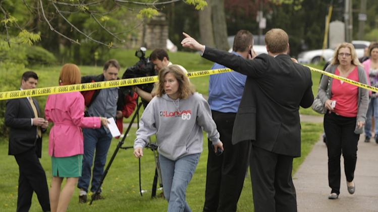 Parents and other family members cross under a police line to check on their children, Monday, April 29, 2013, at LaSalle High School in Cincinnati, where a high school student pulled out a gun and shot himself in a classroom on Monday. The Hamilton County sheriff's office says the youth was taken to a hospital with a self-inflicted wound. They say there apparently was no threat to other students at the private school. (AP Photo/Cincinnati Enquirer, Glenn Hartong) MANDATORY CREDIT;  NO SALES