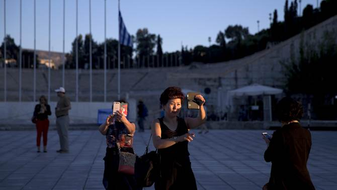 Asian tourists take self portraits with their smart phones outside the marble Panathenian Stadium, where the first modern Olympics was held in 1896, in Athens, Wednesday Oct. 1, 2014. Tour and hoteliers associations have reported a sharp rise in visitors to Athens this year, amid a general boom in Greece, thanks to an increase in international flight services to the Greek capital, lower prices and fewer downtown demonstrations compared to recent years.  (AP Photo/Petros Giannakouris)