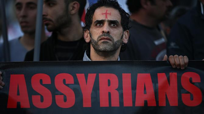 An Assyrian man with a red cross painted on his forehead holds a banner as he walks during a protest of several hundred people in solidarity with Christians abducted in Syria and Iraq, in downtown Beirut, Lebanon Saturday, Feb. 28, 2015. The Islamic State group, which has repeatedly targeted religious minorities in Syria and Iraq, abducted more than 220 Assyrians this week in northeastern Syria. (AP Photo/Hussein Malla)