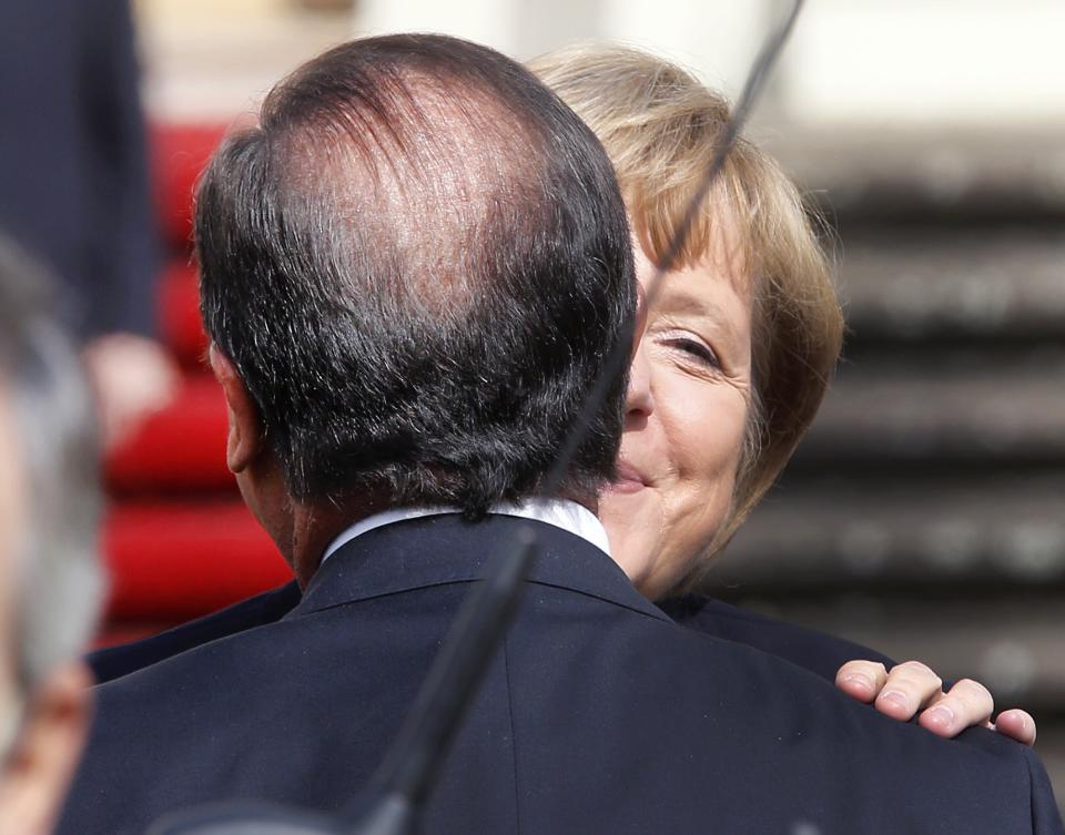 German Chancellor Angela Merkel, right, and French President Francois Hollande welcome each other in front of the castle in Ludwigsburg, Germany, Saturday, Sept. 22, 2012. Merkel and Hollande attend the celebration of the 50th anniversary of former French President Charles de Gaulle's speech to the youth of Germany. (AP Photo/Michael Probst)