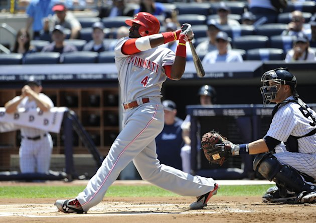 Cincinnati Reds' Brandon Phillips (4) hits an RBI single off of New York Yankees pitcher Ivan Nova as catcher Russell Martin looks on during the first inning of an interleague baseball game on Saturda