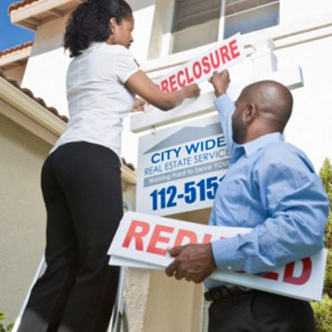 Two-people-putting-up-foreclosure-sign_web