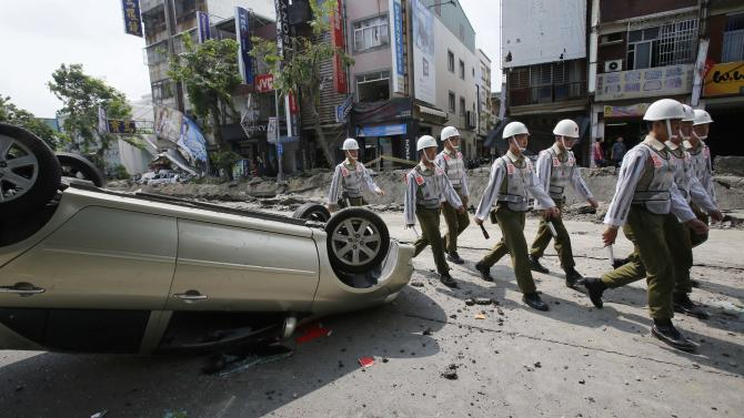Soldiers walk through a street destroyed by a massive gas explosion in Kaohsiung, Taiwan, Friday, Aug. 1, 2014. Scores of people were killed and more than 200 others injured when several underground gas explosions ripped through Taiwan's second-largest city overnight, hurling concrete through the air and blasting long trenches in the streets, authorities said Friday. (AP Photo/Wally Santana)