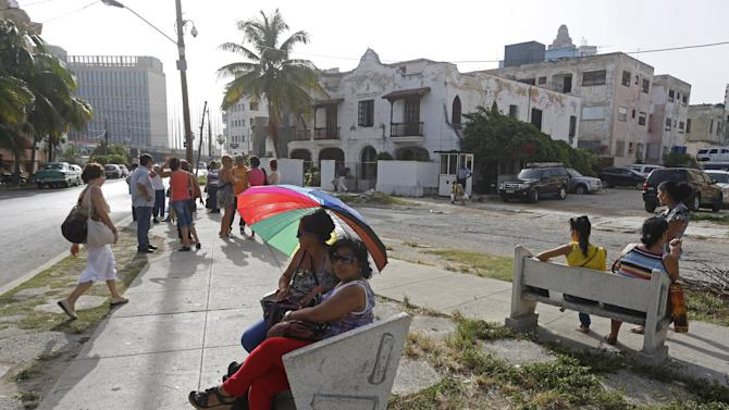 People gather a block away from the U.S. diplomatic mission in Cuba, the U.S. Interests Section, to request for a visa to enter the United States, in Havana