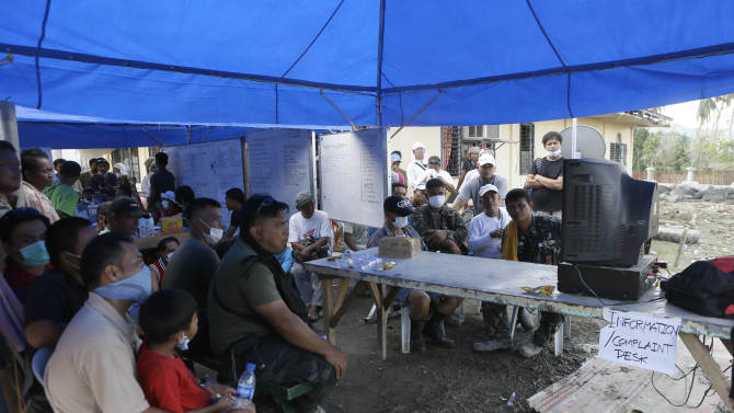 Typhoon victims as well as rescuers and soldiers take a break to watch the fight between the Philippines' Manny Pacquiao and Mexico's Juan Manuel Marquez at the command center for the rescue efforts for typhoon Bopha's victims at New Bataan township, Compostela Valley in southern Philippines Sunday Dec. 9, 2012. Filipino fans were stunned by Pacquiao's knockout defeat to Marquez on Sunday, dampening the spirit of a nation battered by a powerful typhoon that killed more than 600 people in the southern region where the boxing champion lives. (AP Photo/Bullit Marquez)