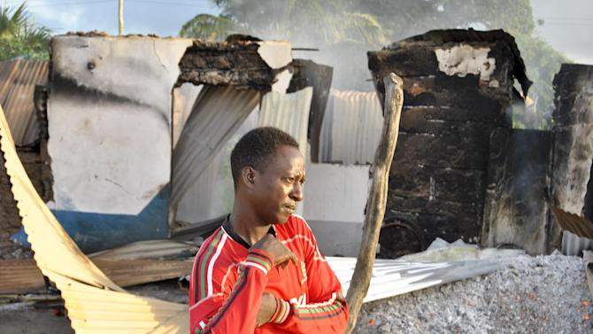 A man stands in front of the still-smouldering shell of a building set on fire by militants in the town of Mpeketoni, about 100 kilometers (60 miles) from the Somali border on the coast of Kenya Monday, June 16, 2014. Dozens of Somali extremists wielding automatic weapons attacked the small Kenyan coastal town for hours, assaulting the police station, setting two hotels on fire, and spraying bullets into the street killing dozens, officials said Monday. (AP Photo)