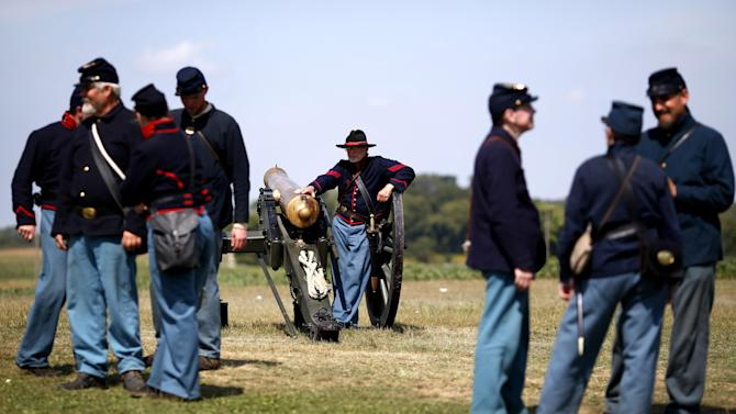 Volunteers portraying Union artillery troops gather before performing a cannon firing demonstration at Antietam National Battlefield in Sharpsburg, Md., Monday, Sept. 17, 2012. A series of demonstrations and speeches took place at the battlefield to commemorate the 150th anniversary of the Civil War's Battle of Antietam. (AP Photo/Patrick Semansky)