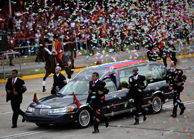 Body guards runs next to the hearse carrying the coffin that contains the remains of Venezuela's late President Hugo Chavez, in a second funeral procession, in Caracas, Venezuela, Friday, March 15, 20