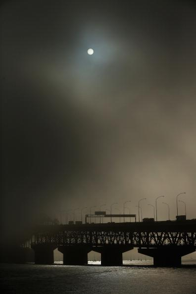 Morning fog shrouds the Auckland Harbour Bridge on July 6, 2012 in Auckland, New Zealand. Fog in Auckland has caused disruption to flights around the country for the second day in a row. (Photo by Phil Walter/Getty Images)