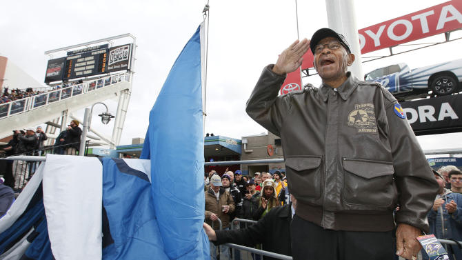 Veteran George Hickman, a Tuskegee Airman during World War II and from Seattle, salutes before he raises the 12th Man Flag before the beginning of the NFL football game against the Ravens as part of the Seattle Seahawks NFL salute to service for military veterans on Veterans Day weekend, Sunday, Nov. 13, 2011, in Seattle. (AP Photo/Elaine Thompson)