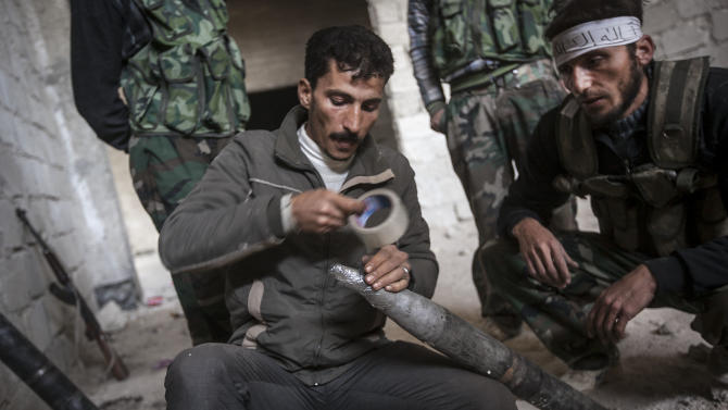 In this Saturday, Nov. 17, 2012 photo, Syrian rebel fighters prepare to fire a homemade rocket as they carry out a coordinated attack by hundreds of rebel fighters on a Syrian air force compound during heavy clashes on the outskirts of Aleppo, Syria. There is a struggle for power among rebel factions in Syria with Islamists rejecting the country's new Western-backed opposition coalition and unilaterally declaring an Islamic state in the key battleground of Aleppo though all of the groups are fighting to topple President Bashar Assad. (AP Photo/Narciso Contreras)