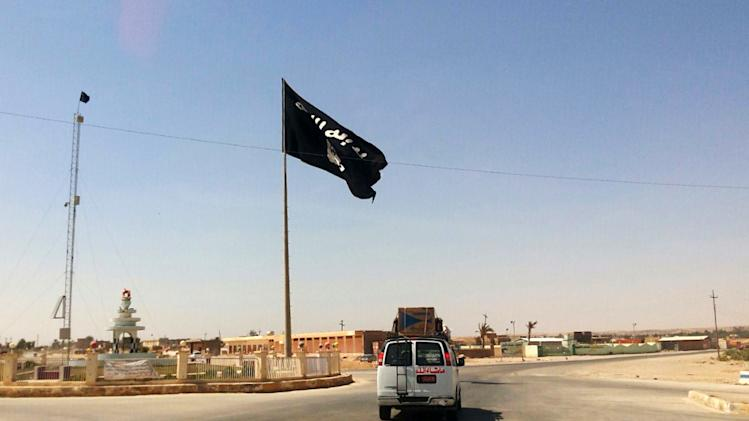 This Tuesday, July 22, 2014 photo shows a motorist passing by a flag of the Islamic State group in central Rawah, 175 miles (281 kilometers) northwest of Baghdad, Iraq, nearly six weeks since a Sunni militant blitz led by the Islamic State extremist group seized large swaths of northern and western Iraq. (AP Photo)