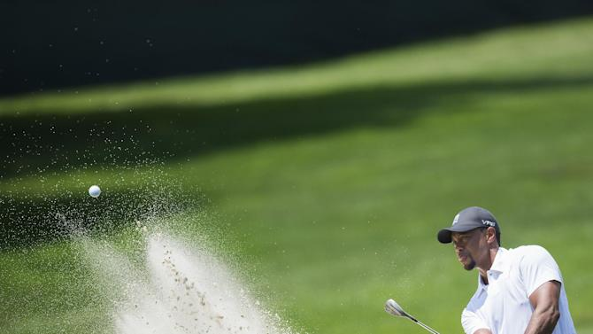 US golfers Tiger Woods swings from a bunker during the second round of the Quicken Loans National at Congressional Country Club in Bethesda, Maryland, June 27, 2014