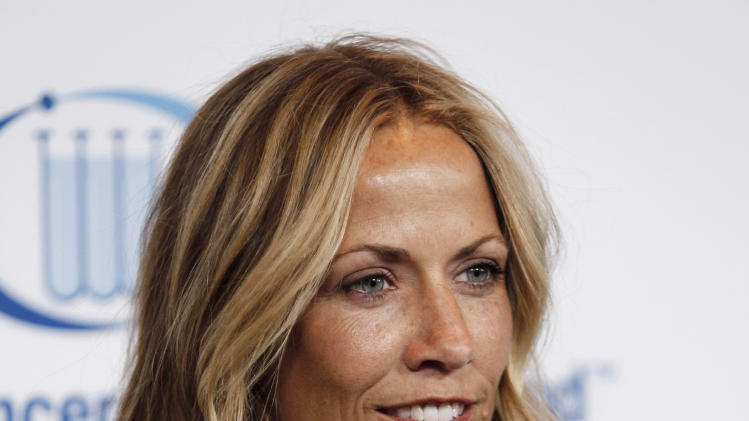 "FILE - This April 18, 2012 file photo shows musician Sheryl Crow at the Entertainment Industry Foundation's ""Unforgettable Evening"" in Beverly Hills, Calif. Crow revealed to an audience that she has a benign brain tumor.  She's currently on a nationwide tour and battled breast cancer several years back. (AP Photo/Matt Sayles, file)"