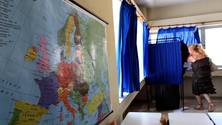 A woman enters a polling booth in front of a map of Europe at a polling station in Athens, Sunday, June 17, 2012. Greeks are voting Sunday for the second time in six weeks in what is arguably their country's most critical election in 40 years. (AP Photo/Petros Giannakouris)