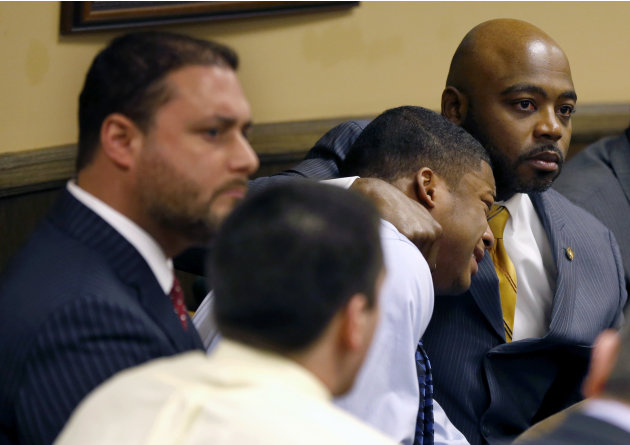 Defense attorney Walter Madison, right, holds his client, 16-year-old Ma'Lik Richmond, second from right, while defense attorney Adam Nemann, left, sits with his client Trent Mays, foreground, 17, as