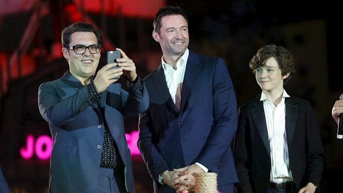 "Actors Hugh Jackman and Levi Miller smile as director Joe Wright takes photos during the blue carpet premiere of ""Pan"" in Mexico City"