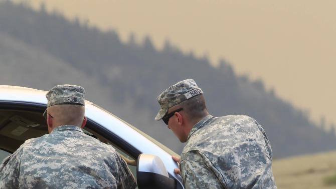 Colorado National Guard members stop a motorist trying to head down Larimer County Highway 74W as a wildfire continues to burn near Livermore, Colo., on Saturday, June 23, 2012. Authorities sent out 992 evacuation notices Friday due to the wildfire burning on more than 100 square miles in northern Colorado as winds pick up. (AP Photo/David Zalubowski)