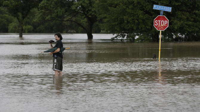 A man photographs floodwaters caused by heavy rains, Saturday, May 25, 2013, in San Antonio. The city has received torrential rains since Friday evening and officials say numerous roads have been closed because of flash flooding. (AP Photo/Eric Gay)